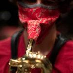 Músicos improvisan máscaras para instrumentos de viento para mantener unida a la banda